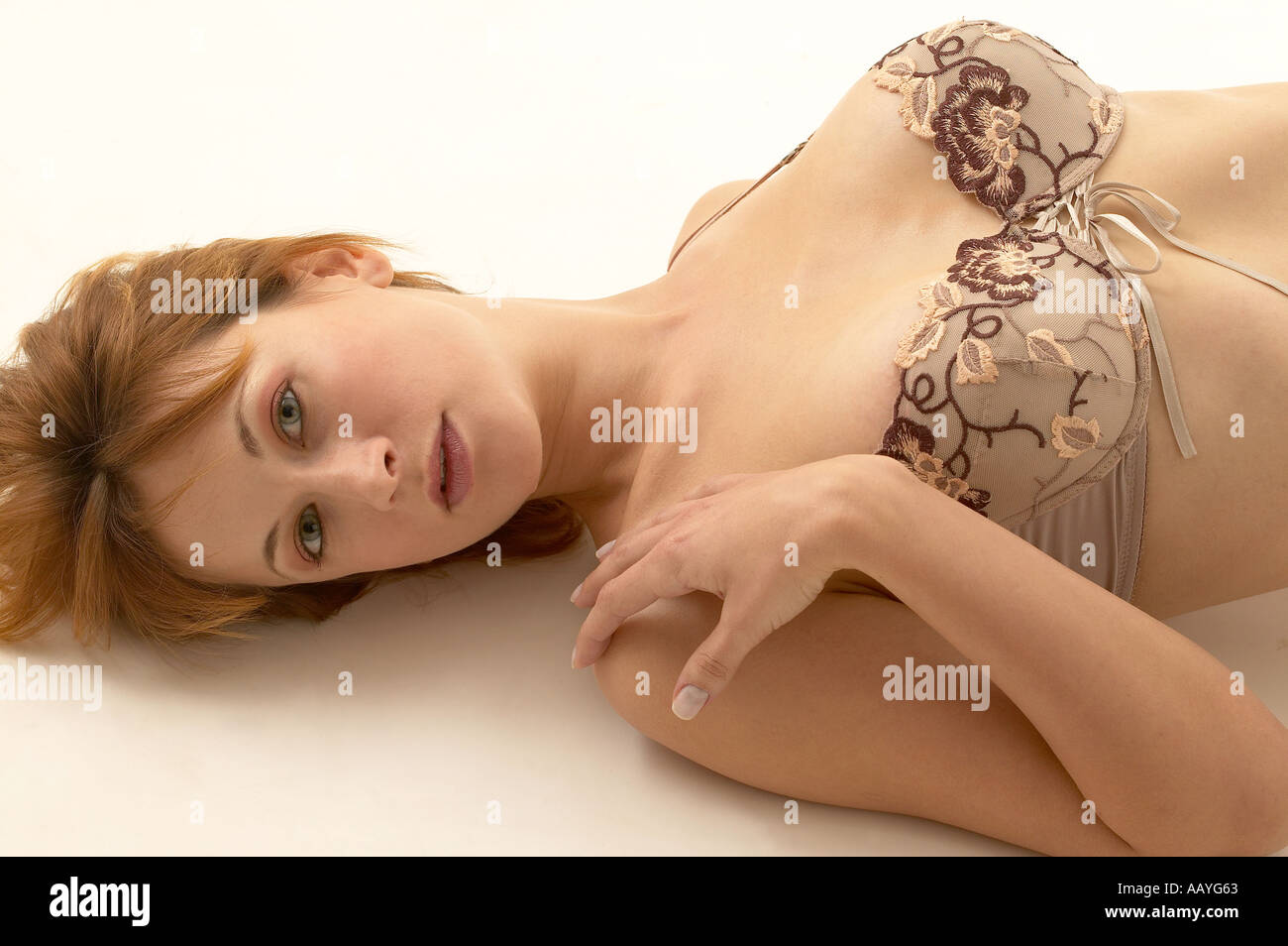 Young model girl woman female with blonde hair wearing skin colour bra sleeping on white background - Stock Image