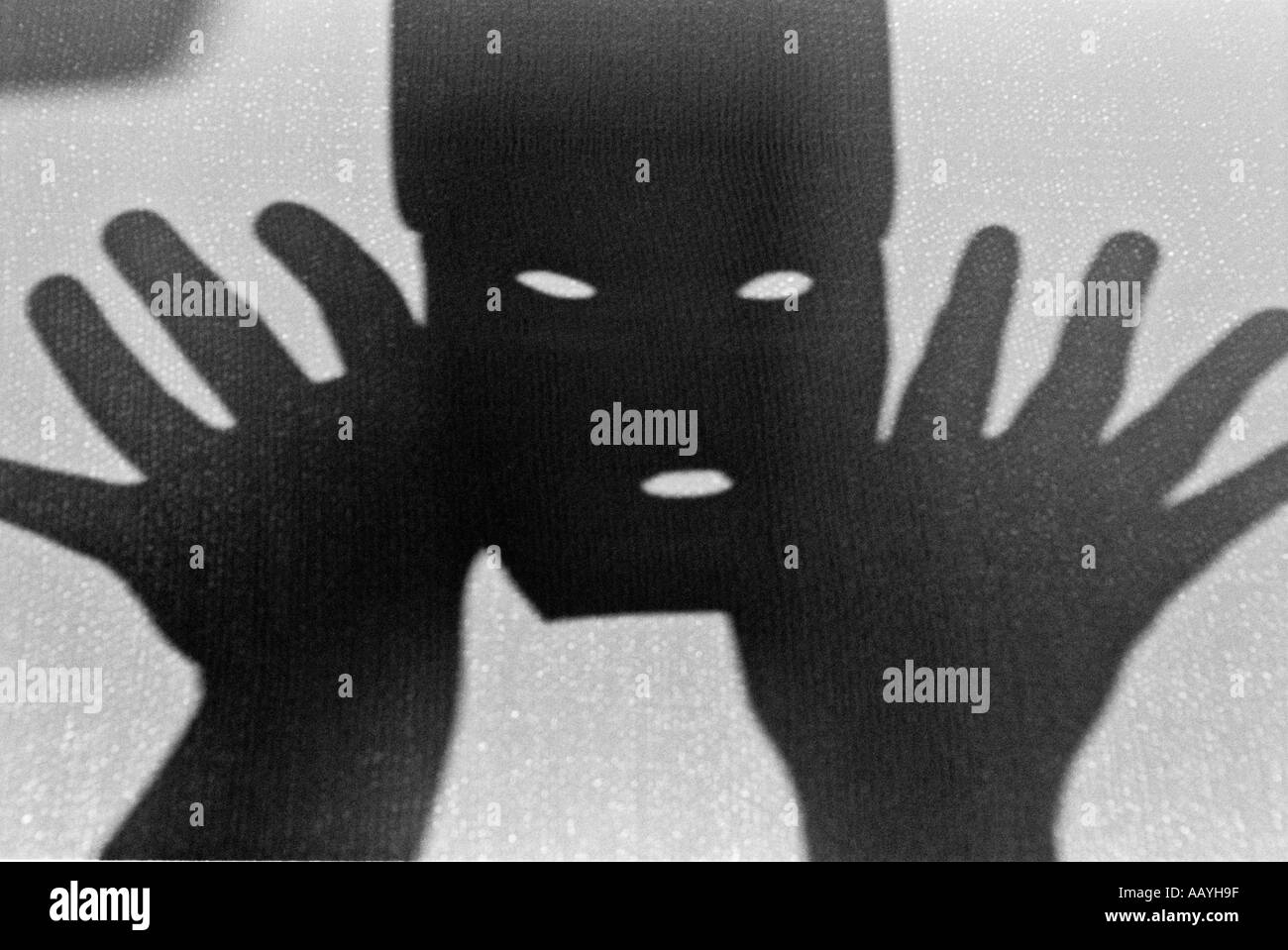 DPA70322 Black and White monochrome horizontal a mask with slit for two eyes and nose to breath in middle of two hands - Stock Image