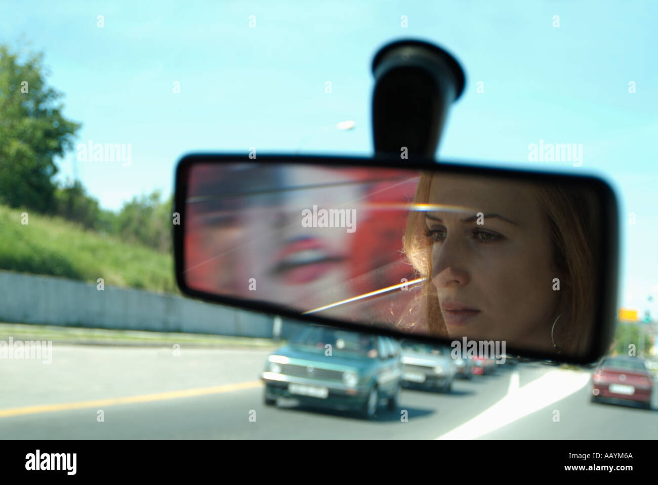Woman in Rear View Mirror of a Car Driving on a Busy Road - Stock Image
