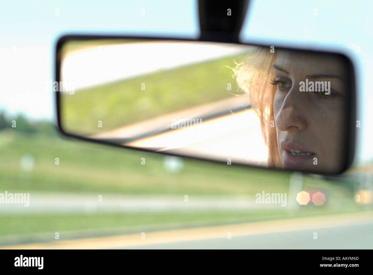 Woman in Rearview Mirror of a Car Driving on a Highway - Stock Image