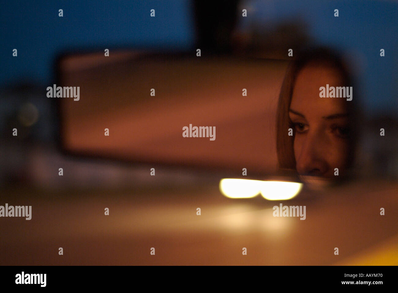 Rear View Mirror with Reflection of a Womans Face in a Car Driving Along a Road at Night Stock Photo