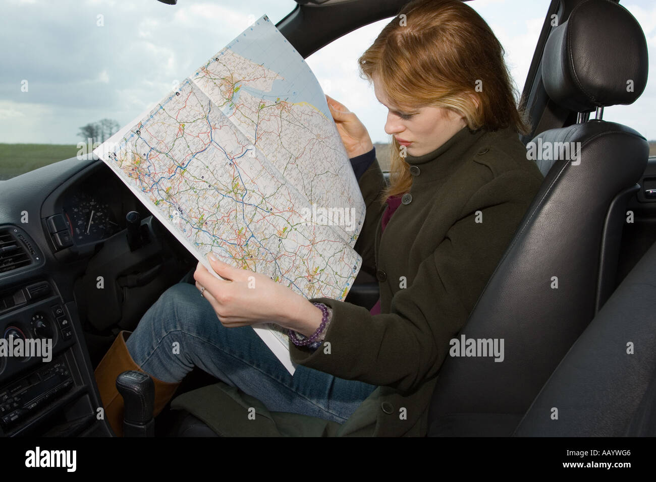 A woman driver reading a map for directions after becoming lost - Stock Image