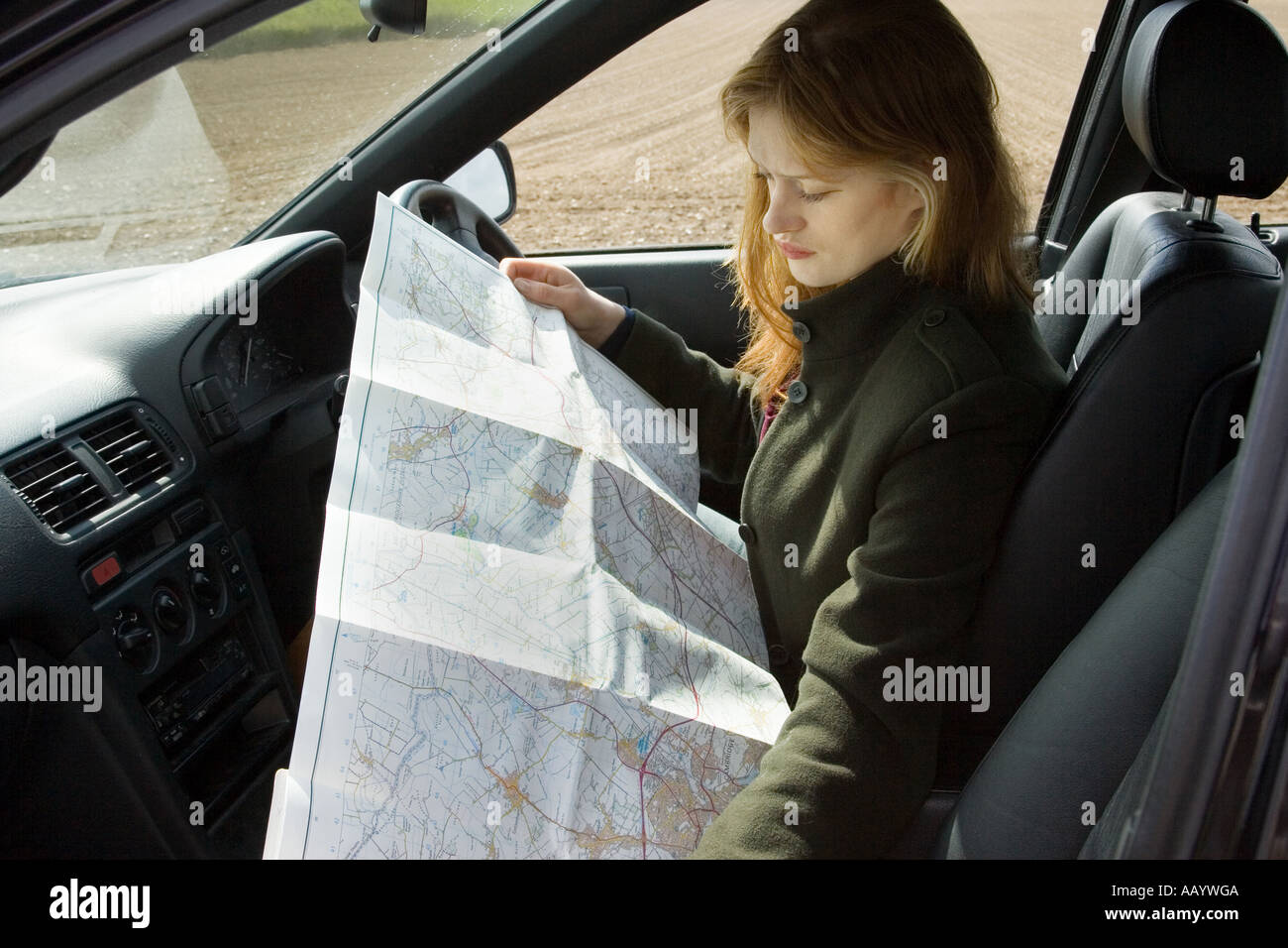 A woman driver reading a map for directions after becoming ... on car services, car trip, car history, car world bugatti veyron, car road map, car map parts, car driving map,