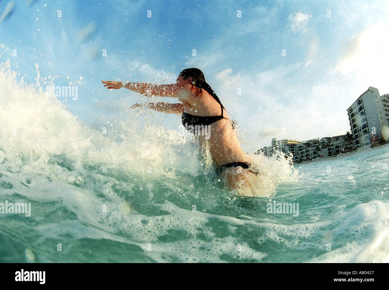 Woman in bikini swimming in waves in Cancun Quintana Roo Mexico Model released image - Stock Image