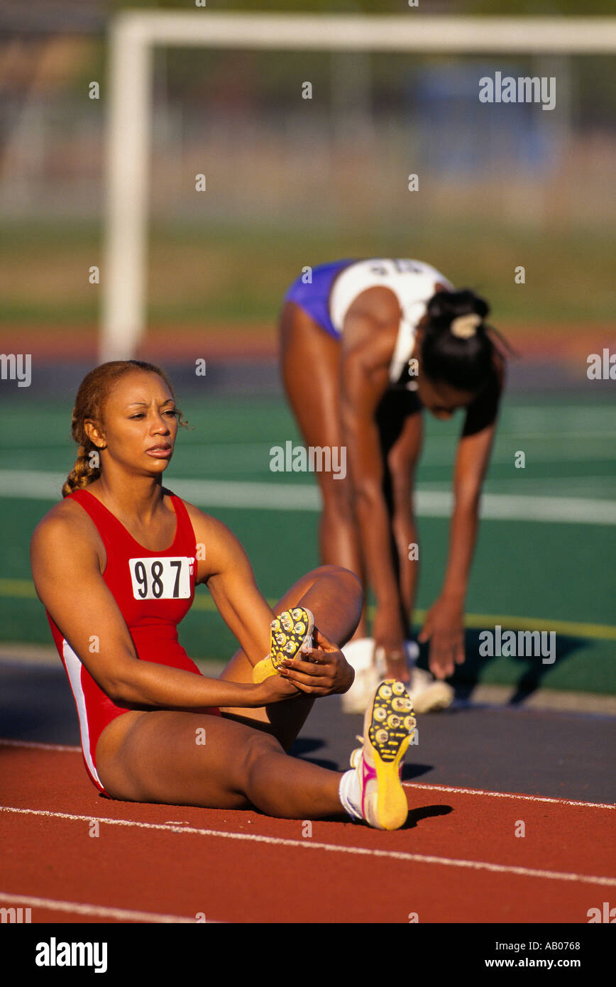 Two African American women track runners stretch before the start of a race - Stock Image