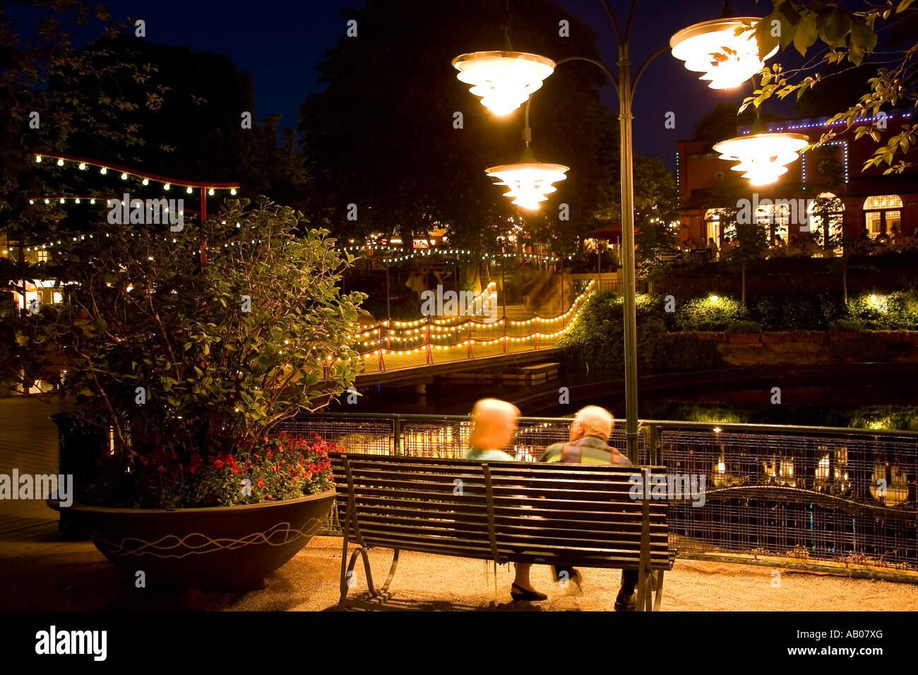 Two people enjoying the summer night at the lake in Tivoli Copenhagen - Stock Image