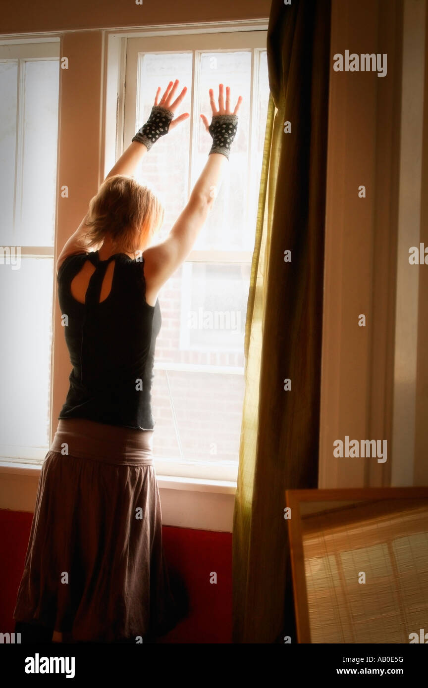 Woman standing in front of window - Stock Image