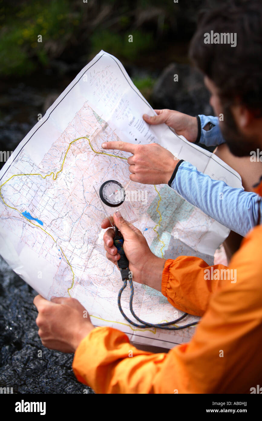 Hikers looking at map and compass - Stock Image