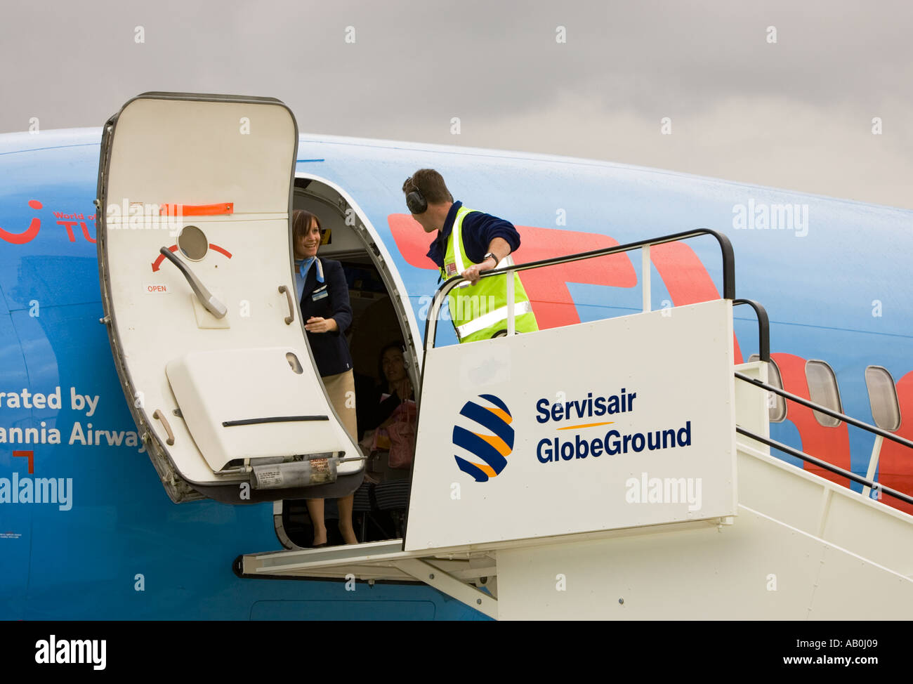 Ground Handling service personnel position steps to door of Boeing 737 that has just landed and talks to stewardess UK & Ground Handling service personnel position steps to door of Boeing ...