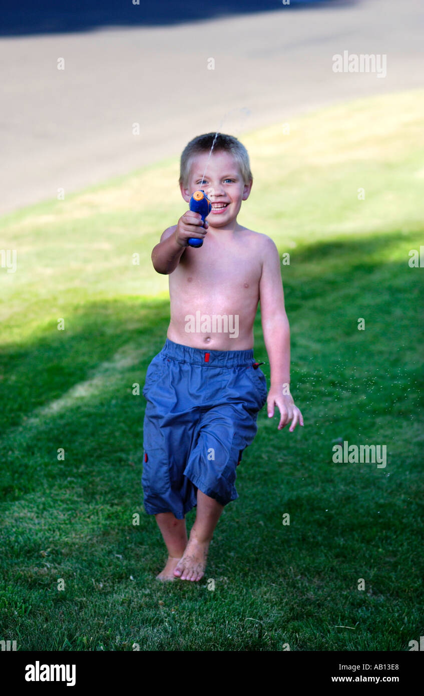 Boy playing with squirt gun - Stock Image