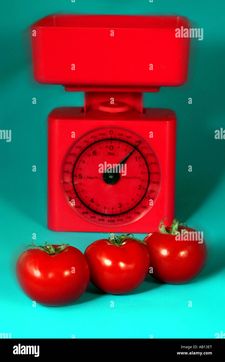 Tomatoes and red kitchen scales - Stock Image