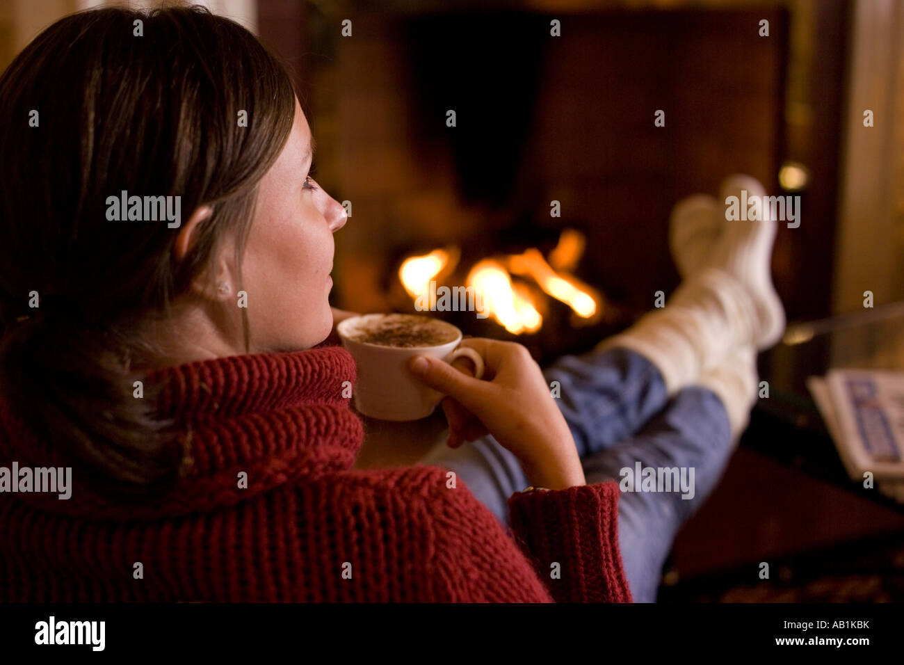 woman with hot drink by fireside - Stock Image
