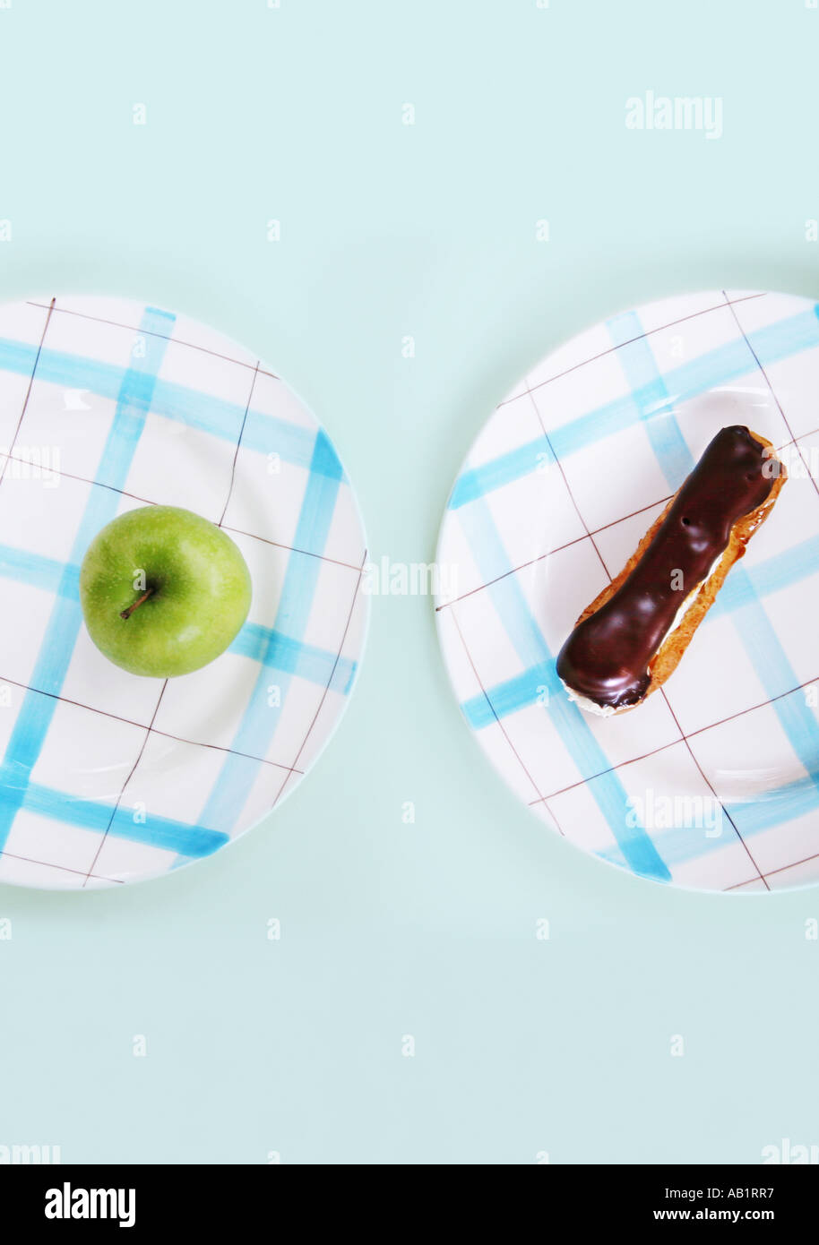 a chocolate eclair and an apple on separate plates - Stock Image