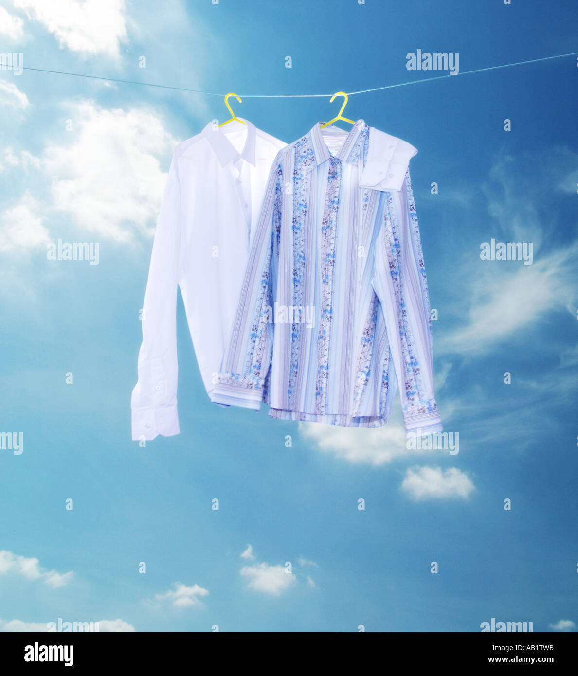 two shirts on a washing line with an arm around each other - Stock Image