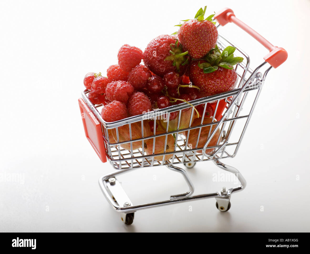 Assorted berries in toy shopping trolley FoodCollection - Stock Image