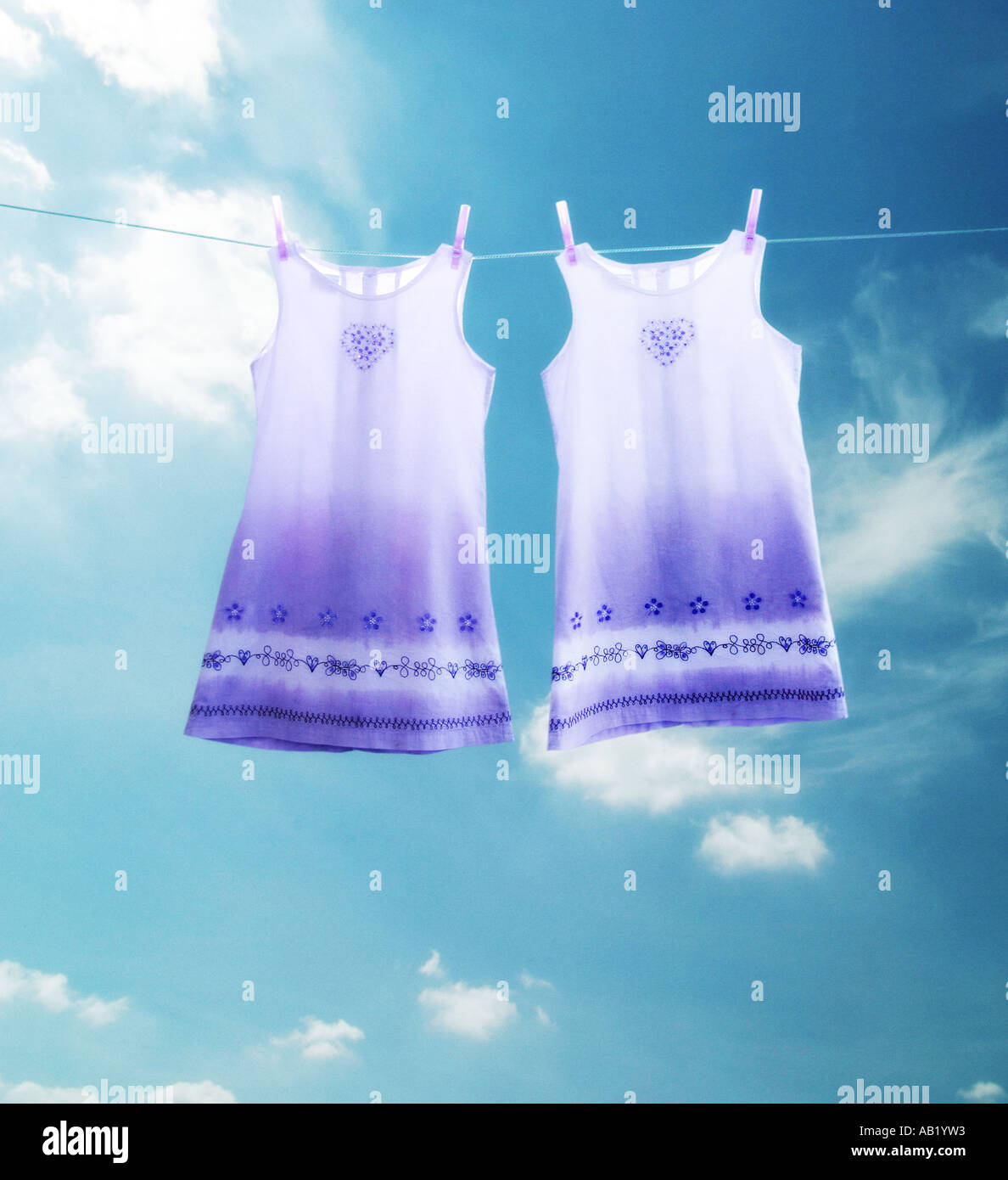 identical dresses hanging on a washing line - Stock Image