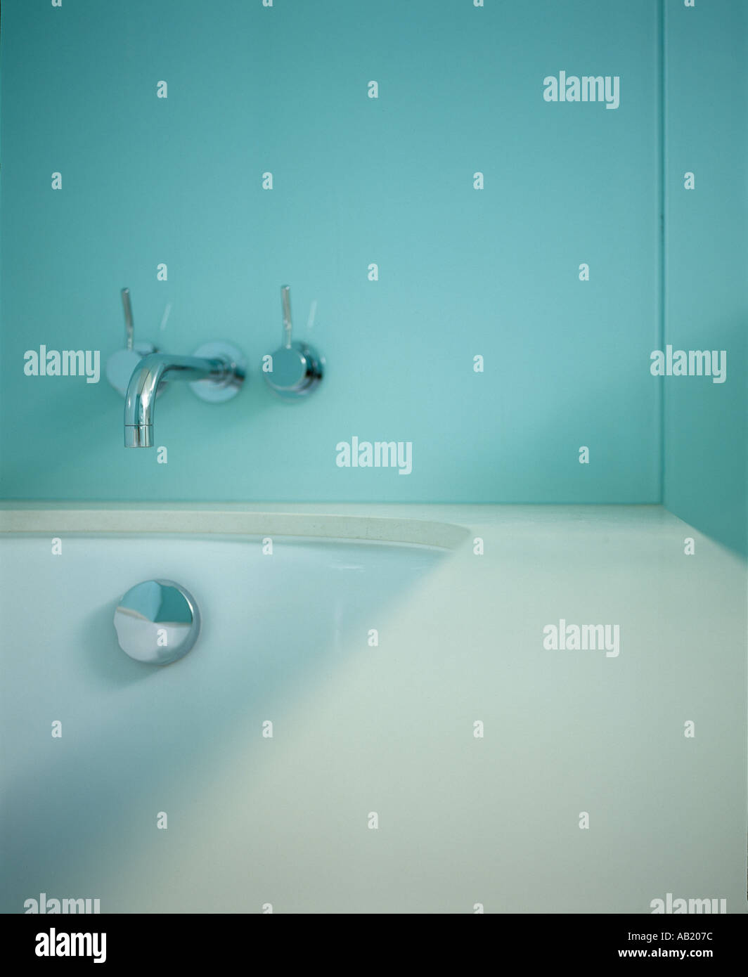 Modern chrome bath mixer  tap by  'vola'  on a green wall at the end of a bath with chrome overflow. - Stock Image