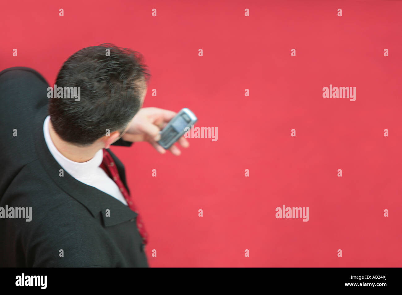 manage with a mobile phone on a red carpet Manager mit Handy auf einem roten Teppich - Stock Image