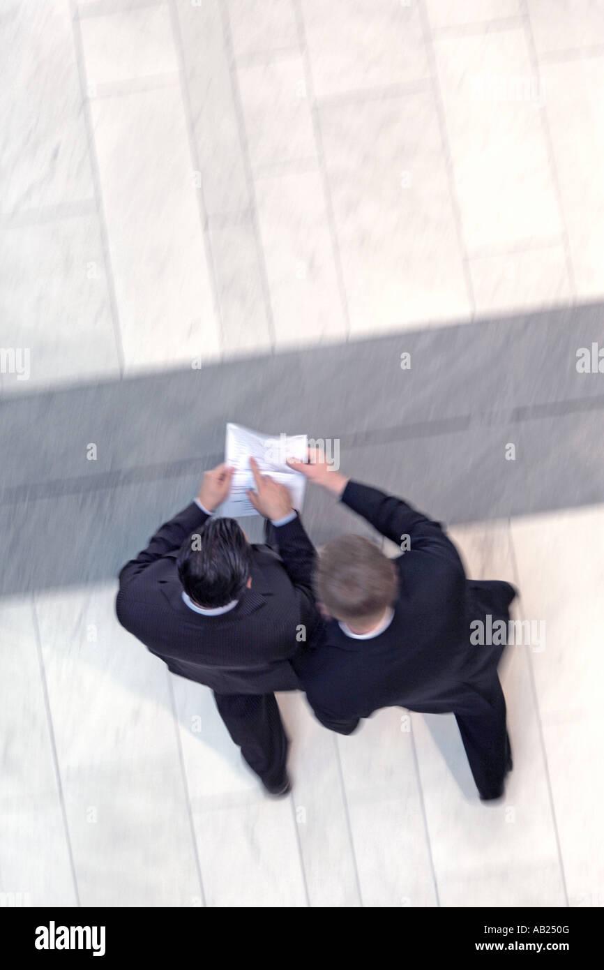 2 manager from above reading something written on a paper 2 Manager von oben die gemeinsam im Gehen ein Dokument - Stock Image