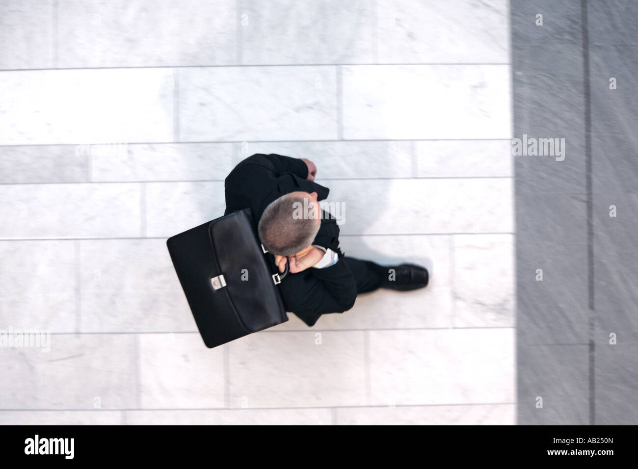 manager in a suit walking with briefcase from above Manager im Anzug mit Aktentasche - Stock Image