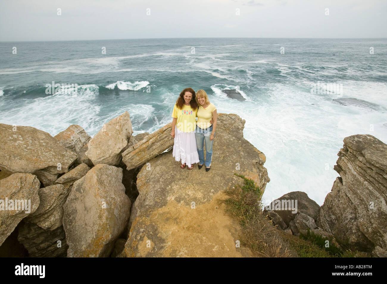 Two women pose at Cruz do Remedios near Peniche west coast of Portugal - Stock Image
