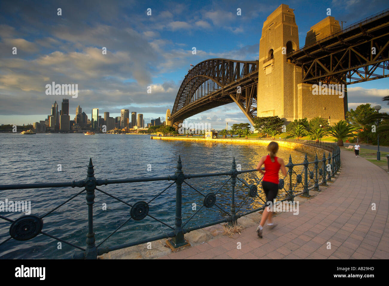 A Jogger Running At Milsons Point With The Harbour Bridge City
