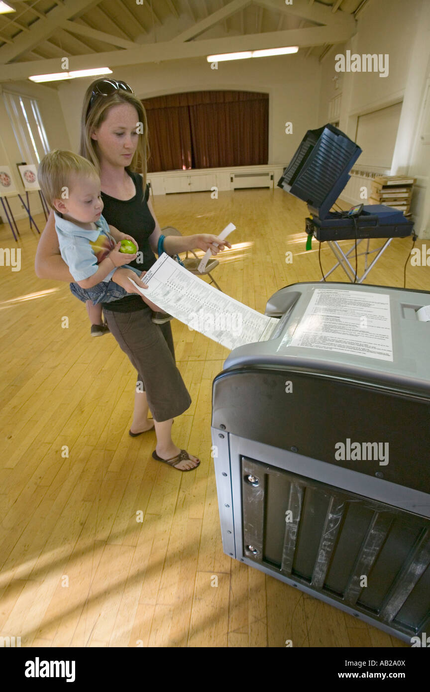 Young mother and Baby Sophia Larson inserts completed ballot for Congressional election November 2006 into an electronic - Stock Image