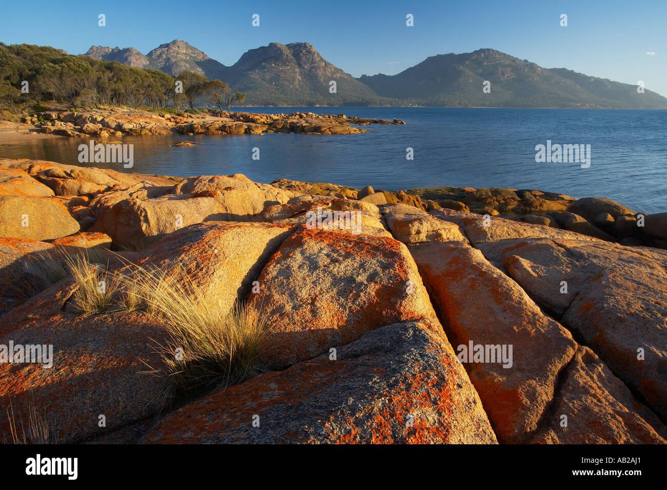 red lichen on rocks Coles Bay with the Hazards beyond Freycinet Peninsula Freycinet National Park Tasmania Australia - Stock Image