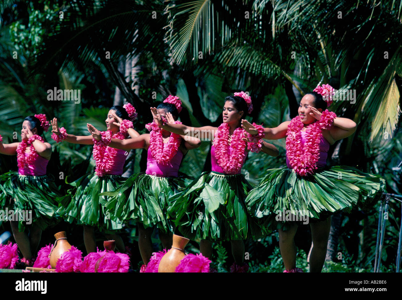 Five hula dancers in grass skirts and pink leis perform Hula Awana modern Hula dance outdoors Haleakala Hawaii - Stock Image