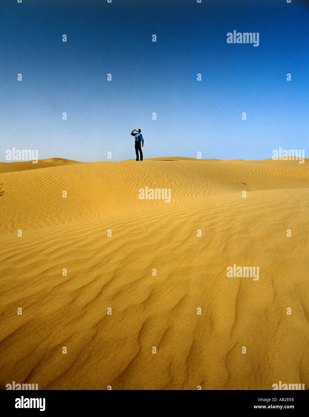 Man in desert drinking from a bottle - Stock Image