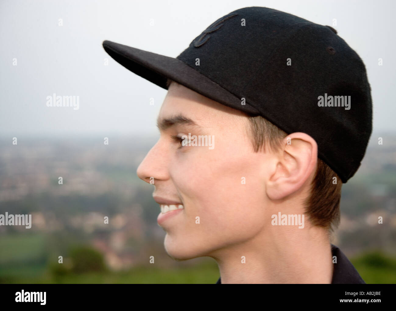 Young man wearing baseball cap smiling portrait side view close up ... ad07652a883