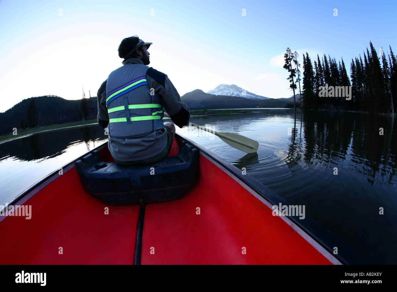 Man paddling canoe on lake - Stock Image