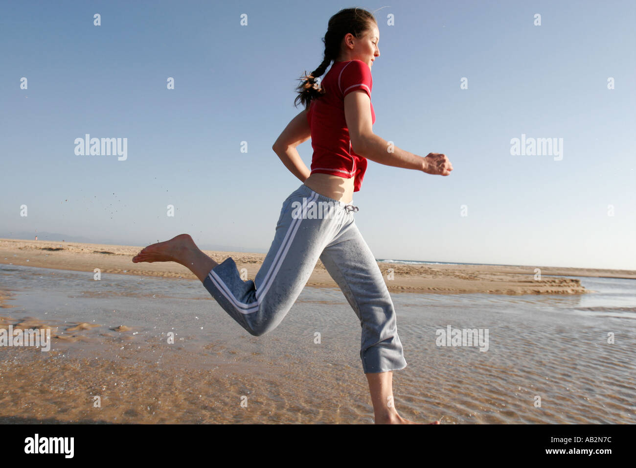 young woman runner in action on the beach - Stock Image