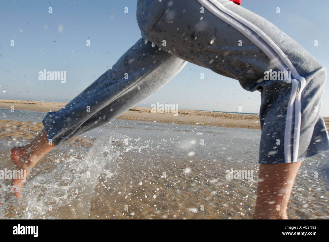 female runner in action on the beach - Stock Image