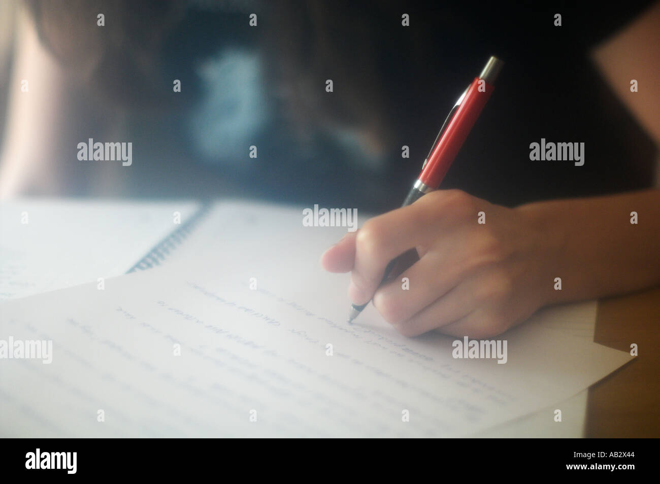 Writing A young left handed woman writing - Stock Image