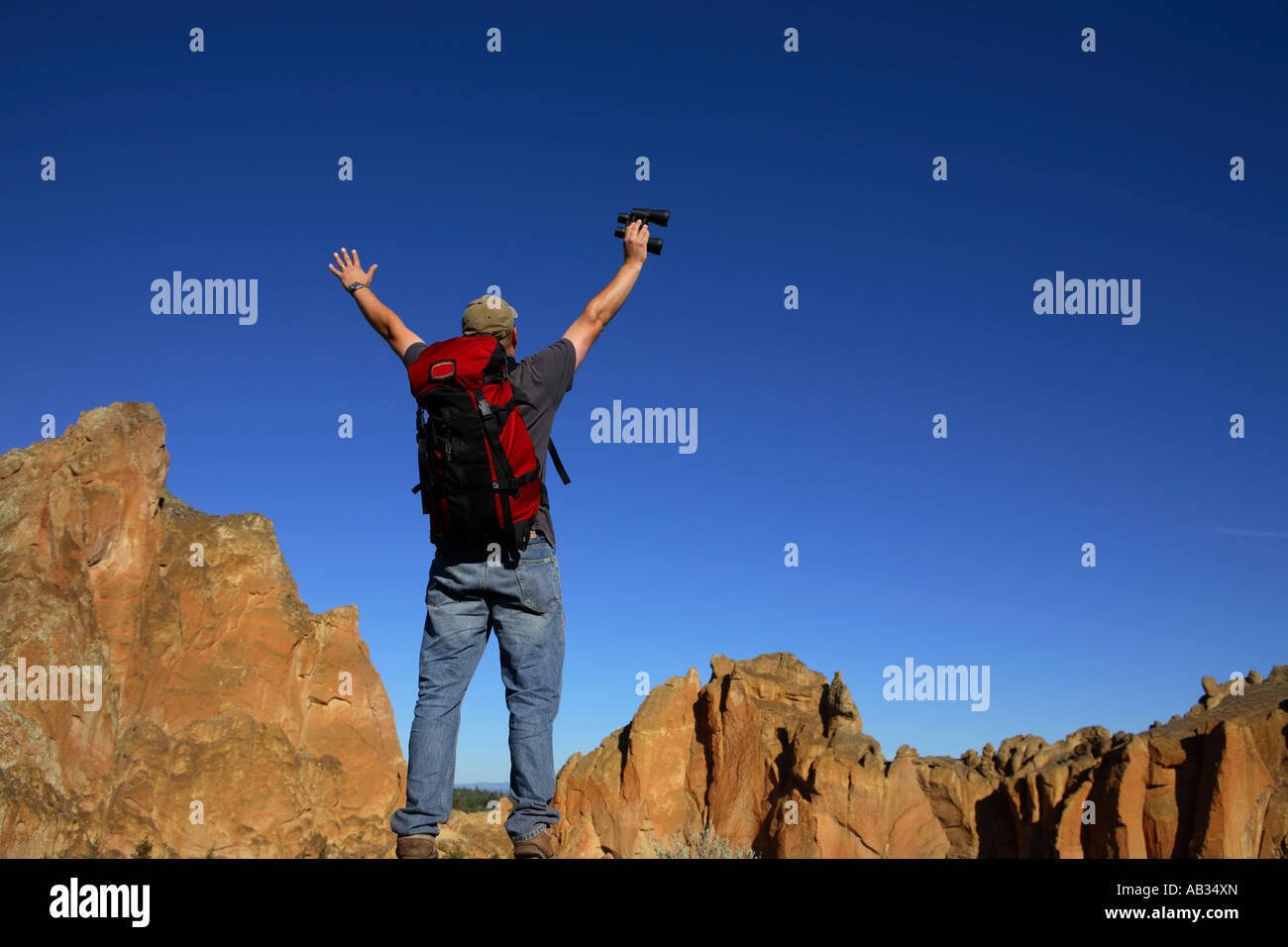 Man wearing backpack stands with hands in air over rocky scenery - Stock Image