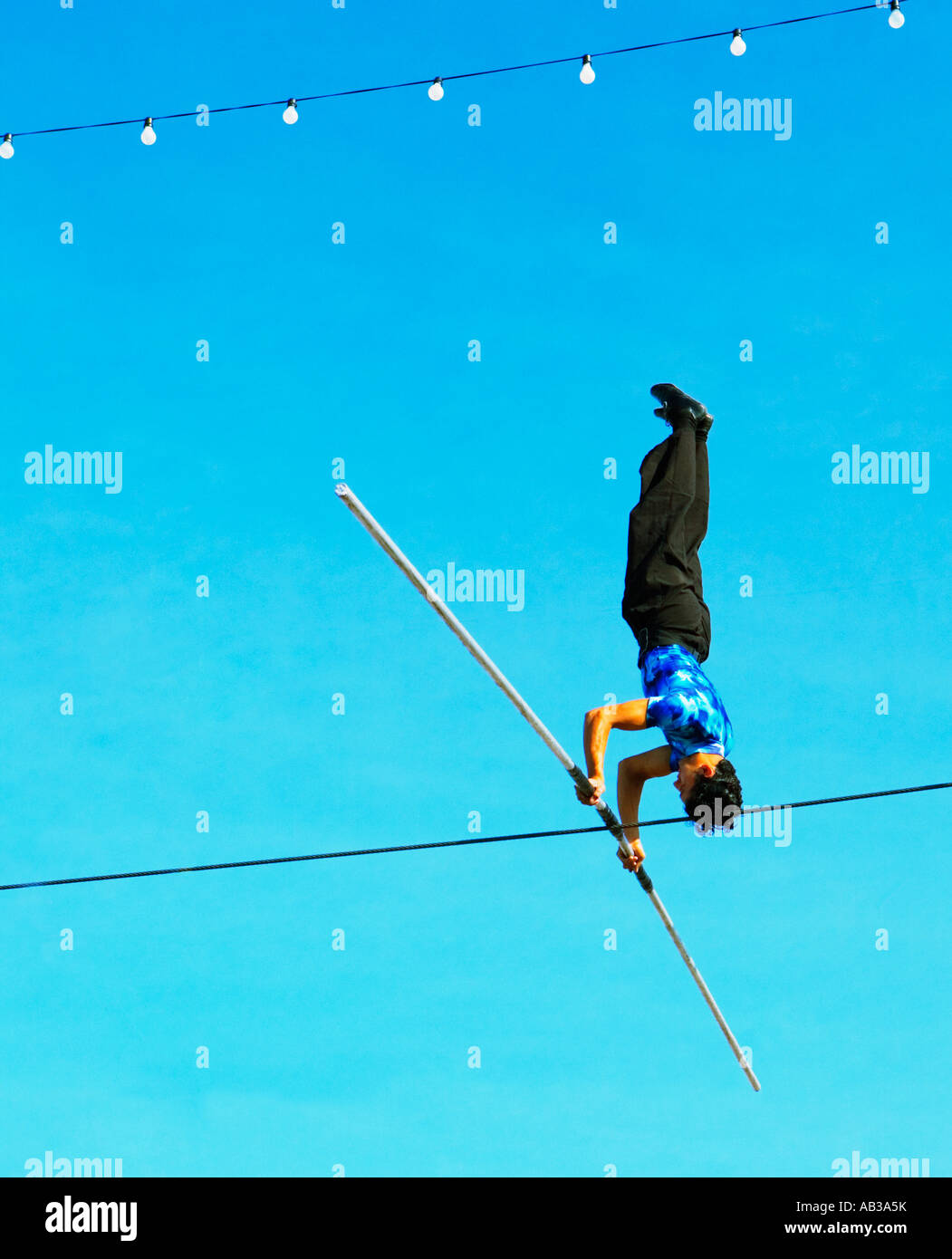 high wire walker doing headstand set against blue sky Stock Photo ...