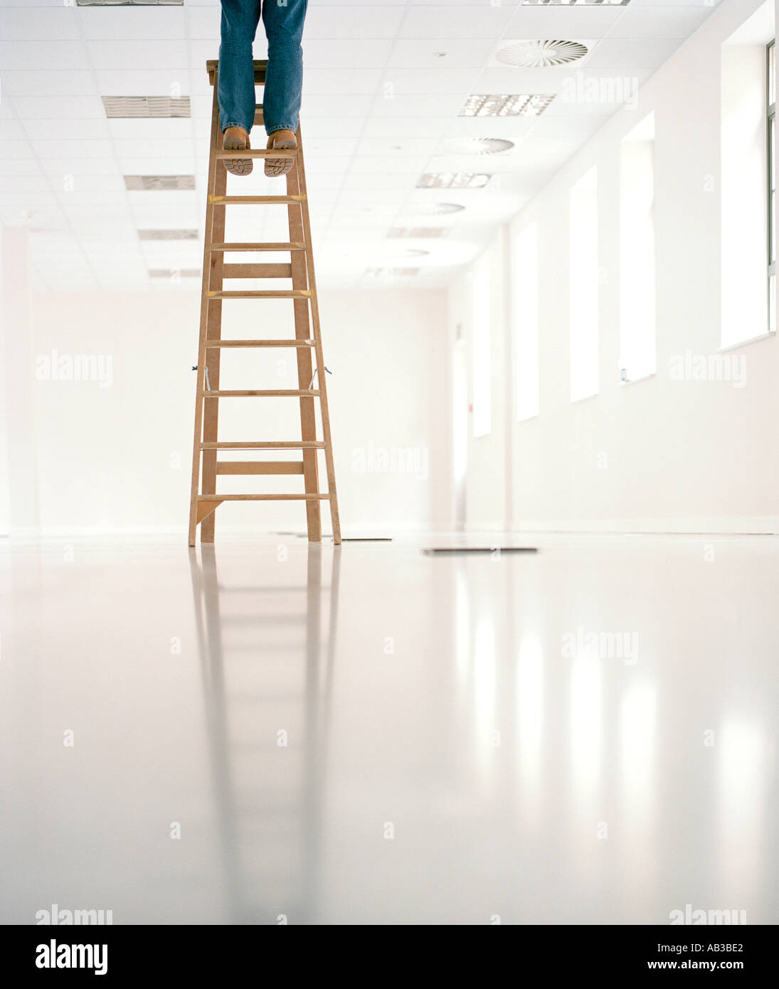 man standing on top of ladder in empty office - Stock Image