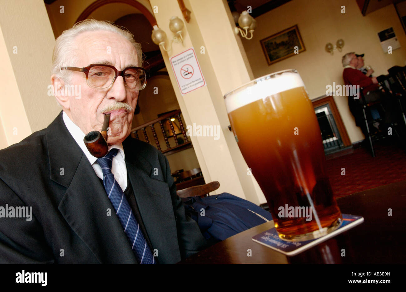 Elderly man sucking on his unlit pipe because of No Smoking in pub Crumlin South Wales UK - Stock Image