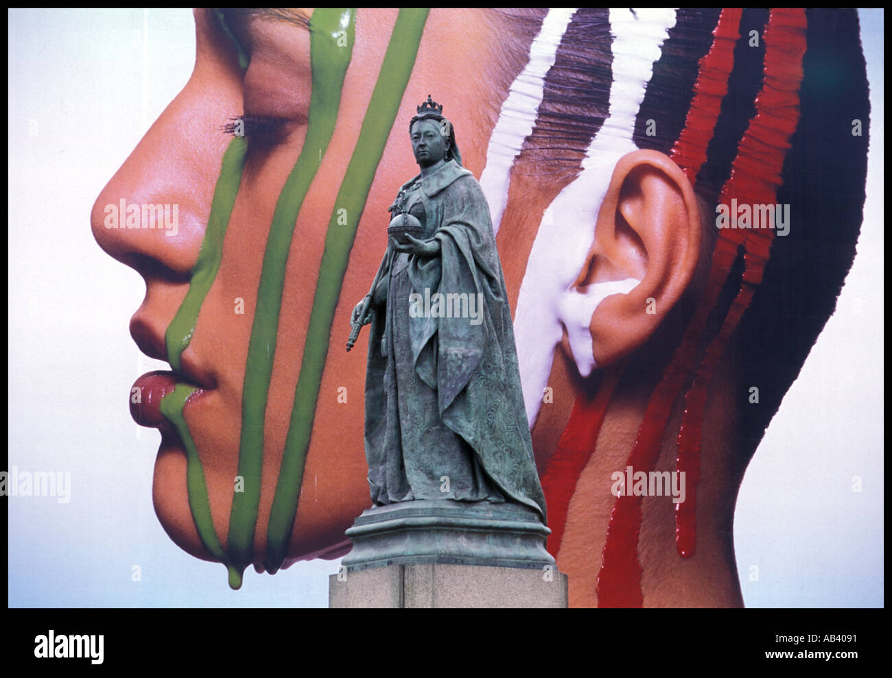 A statue of Queen Victoria against the backdrp of advertising Birmingham England UK - Stock Image