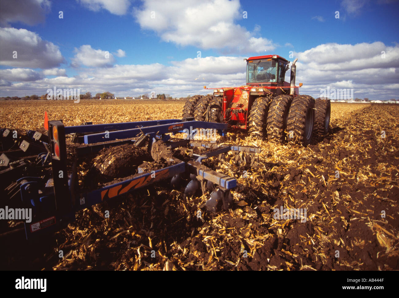 Agriculture - 4WD tractor chisel plowing a field of corn stubble in Autumn in preparation for the Winter dormant period / Wiscon - Stock Image