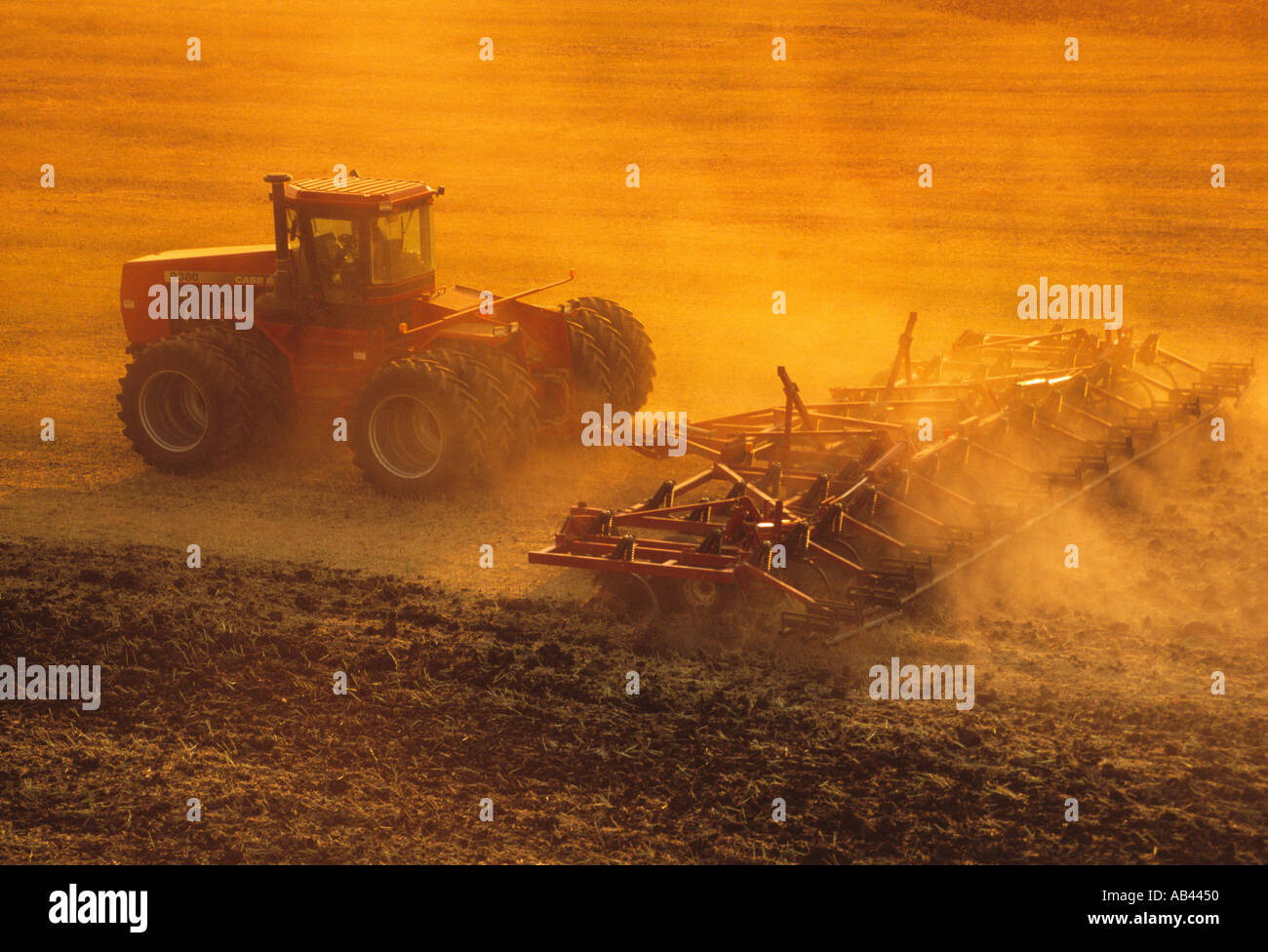 A tractor pulling a springtooth harrow prepares a field of post-harvest wheat stubble for Winter fallow period /Manitoba, Stock Photo