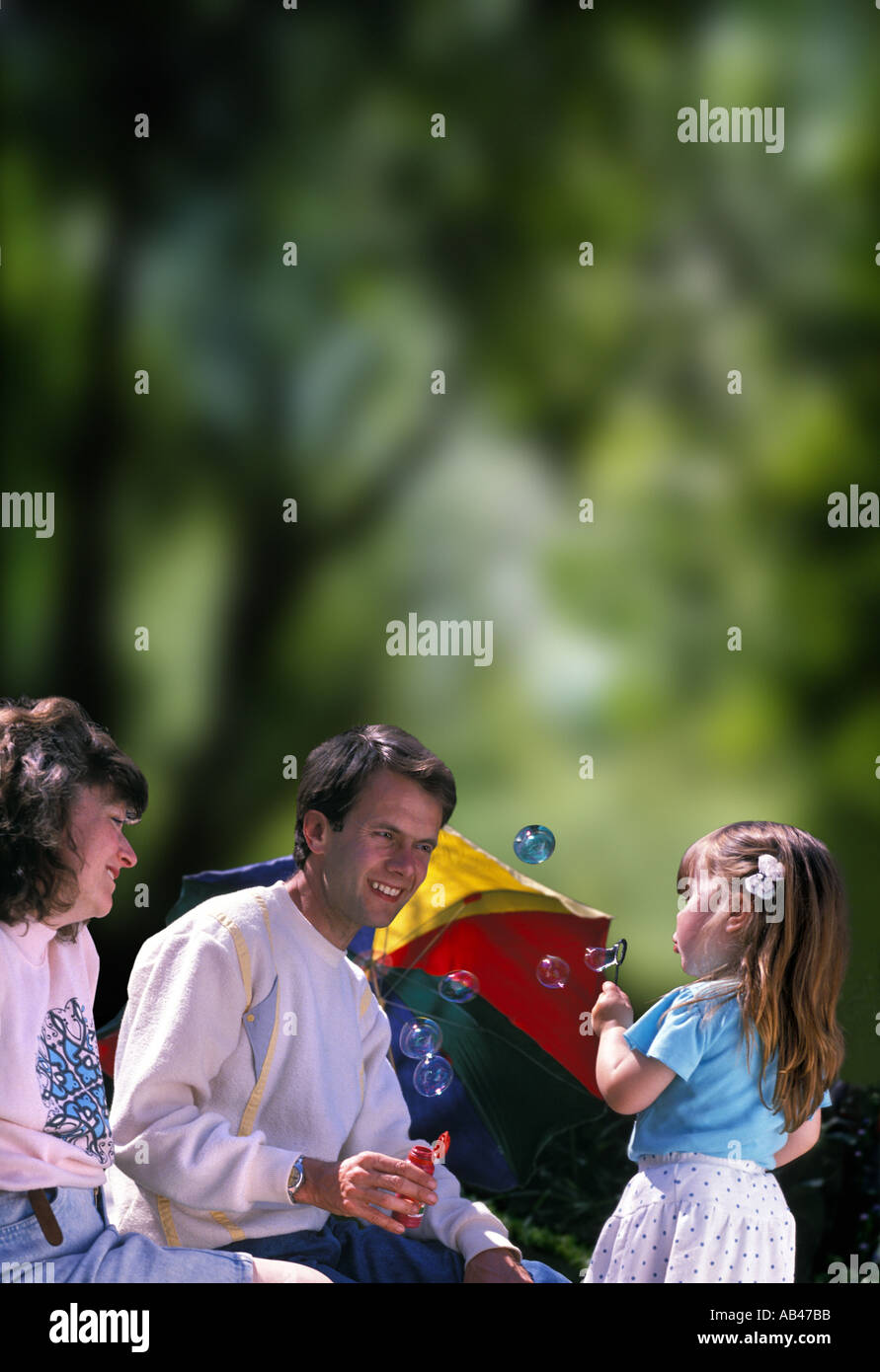 parents with young daughter blowing soap bubbles - Stock Image