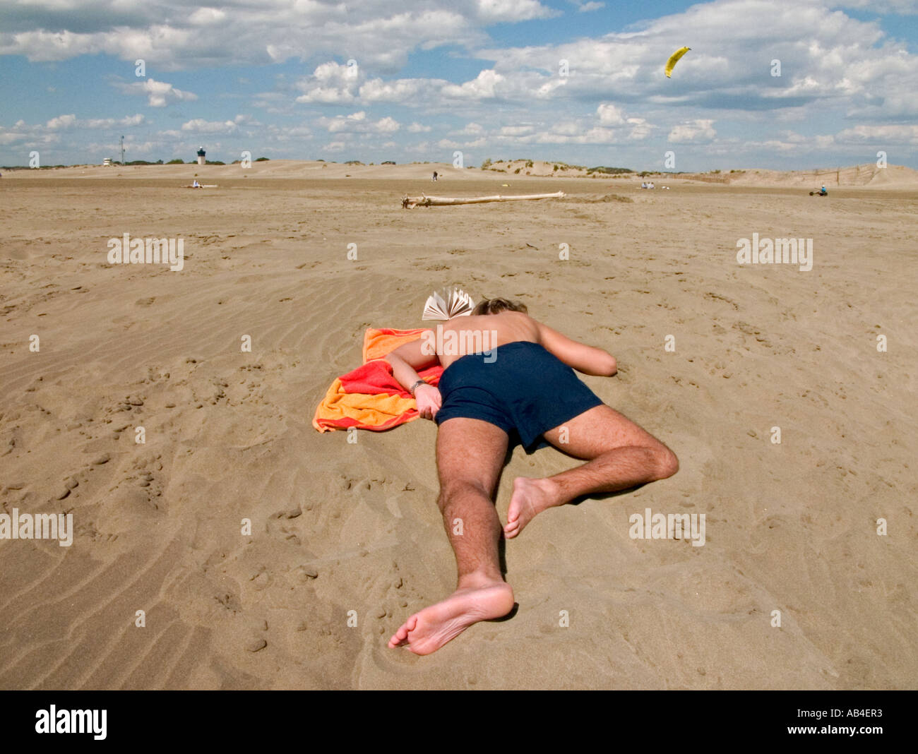 a young man lies on his front on beach towel with  open book - Stock Image