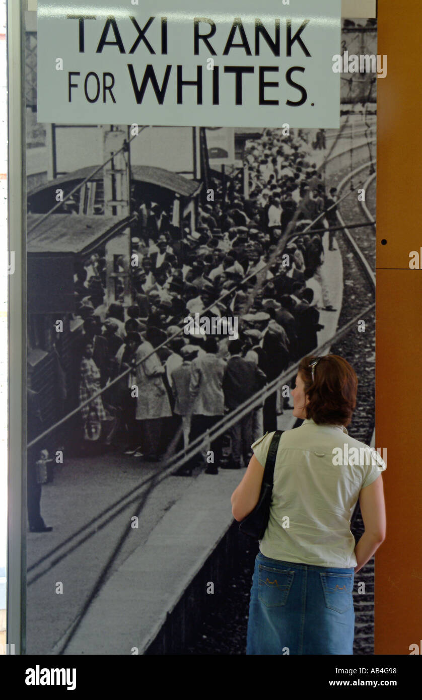 A tourist looks at old pictures on display at the Apartheid Museum. Johannesburg, South Africa - Stock Image