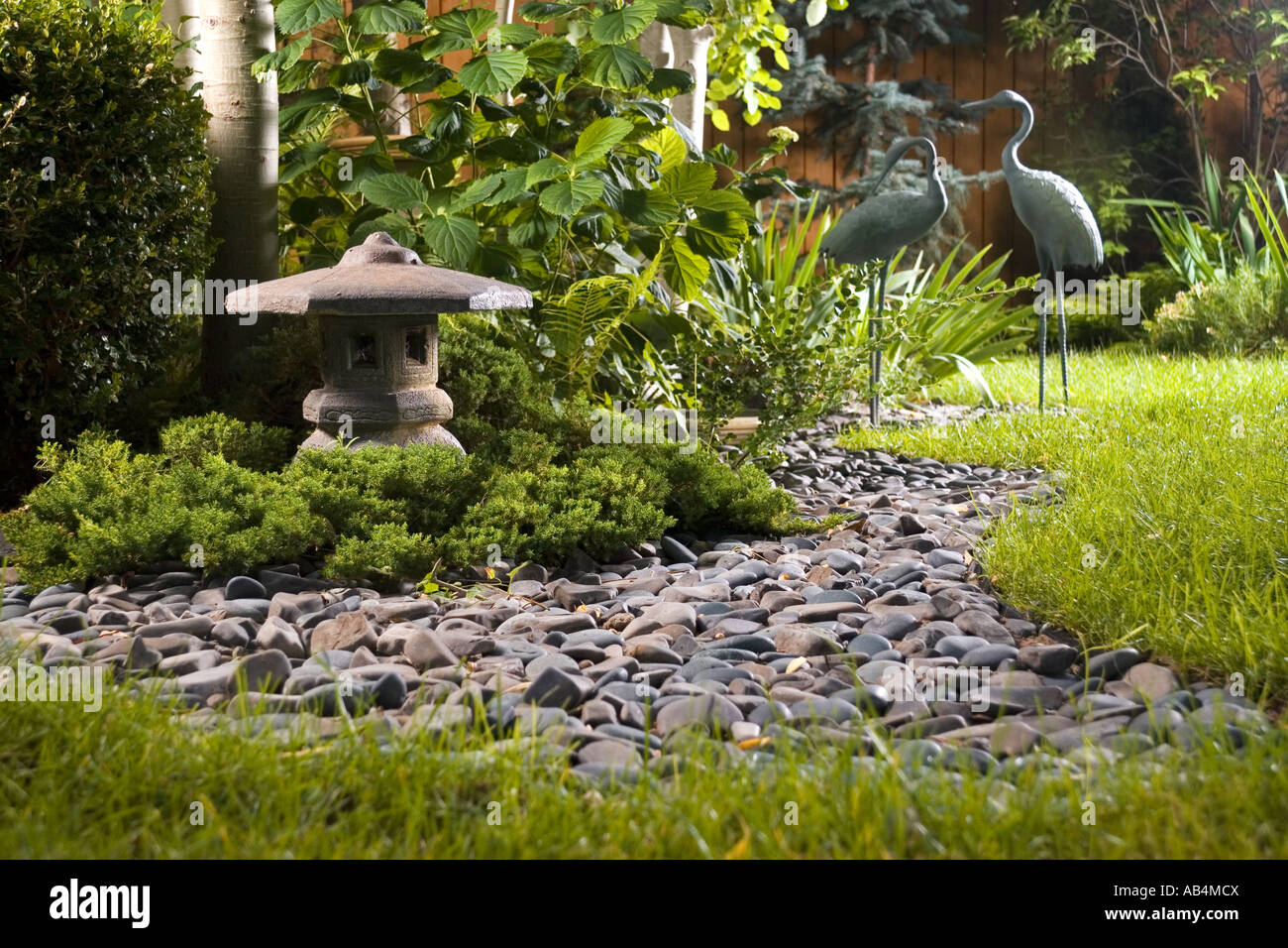 a backyard japanese garden with a dry stream bed lantern