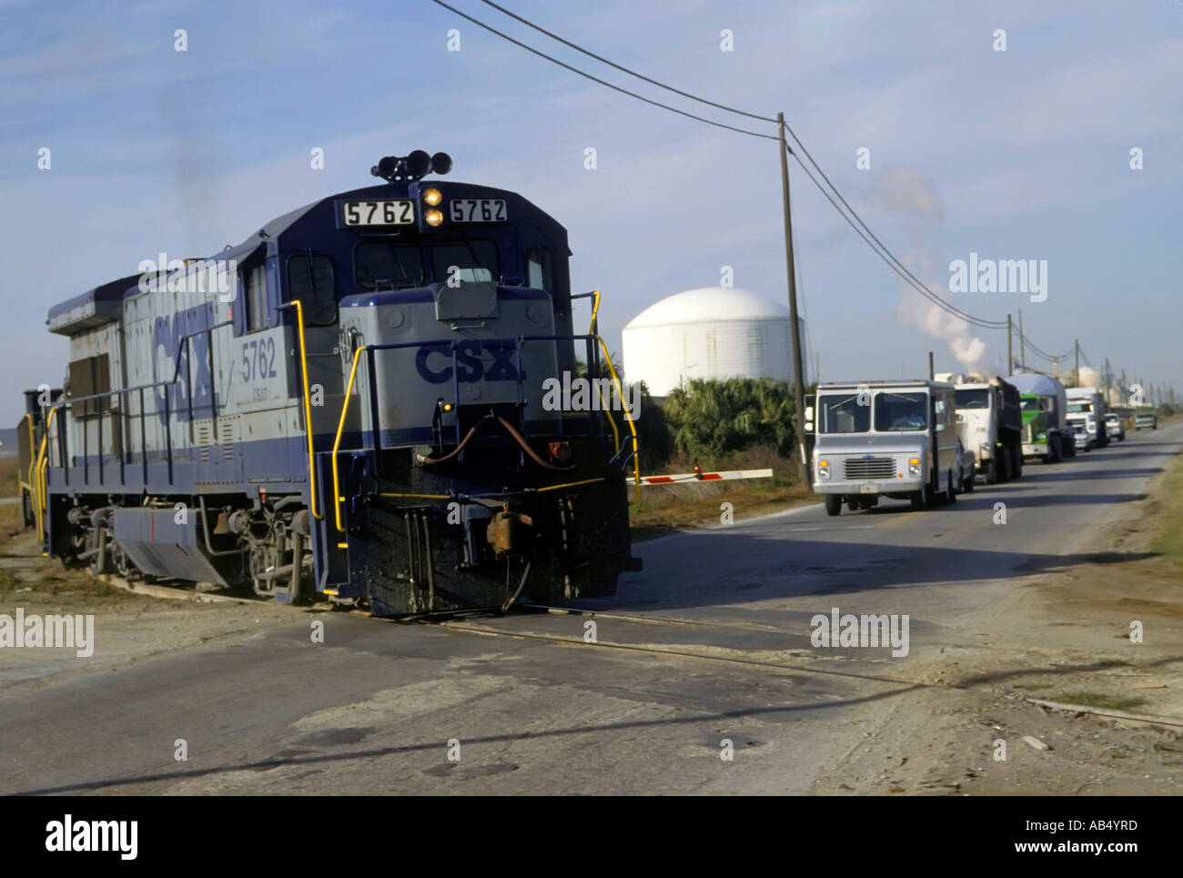 Railroad crossing with diesel train crossing a highway and