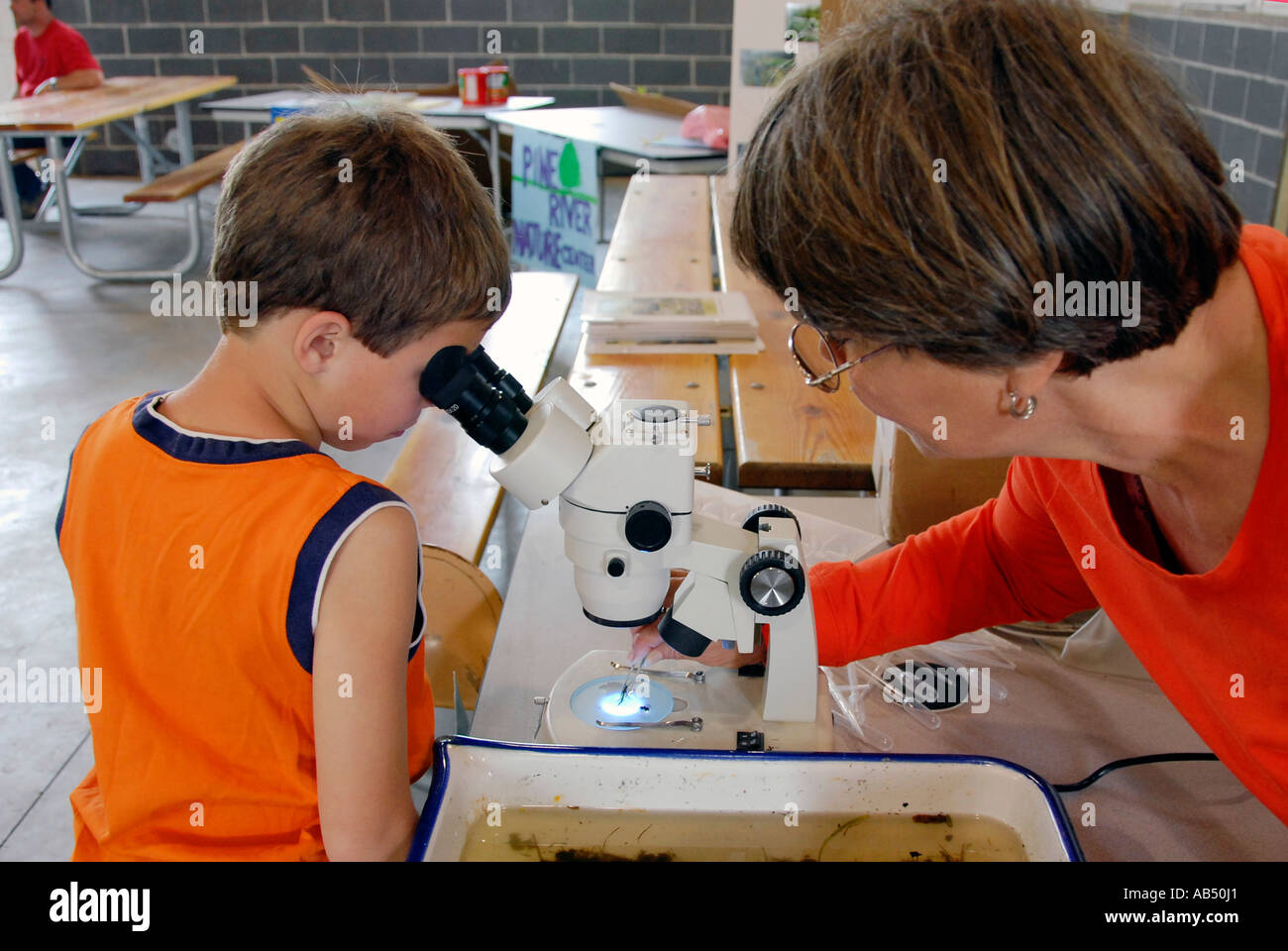 Children look through a microscope at the life in a pond at an Earth Day Festival - Stock Image