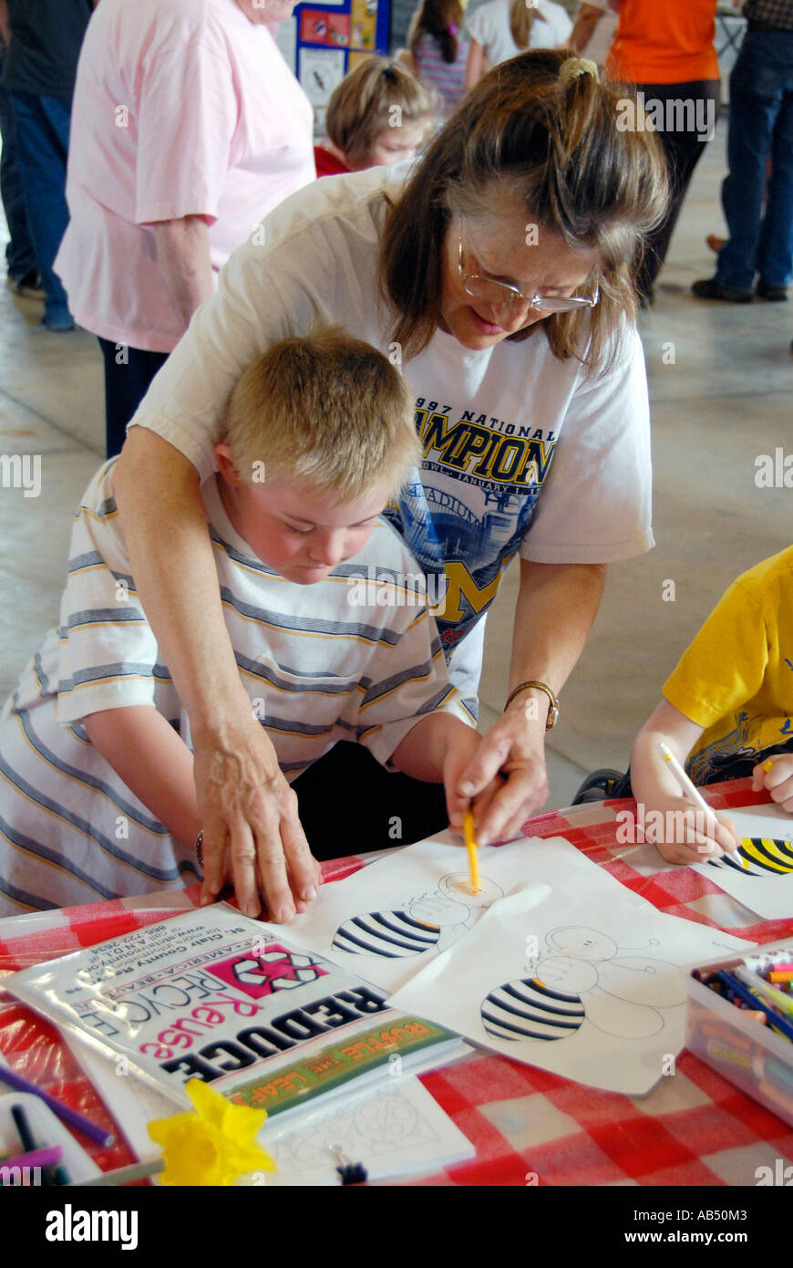 Mentally challenged youth colors a bumble bee at Earth Day Festival invites children and adults to learn about the ecology - Stock Image