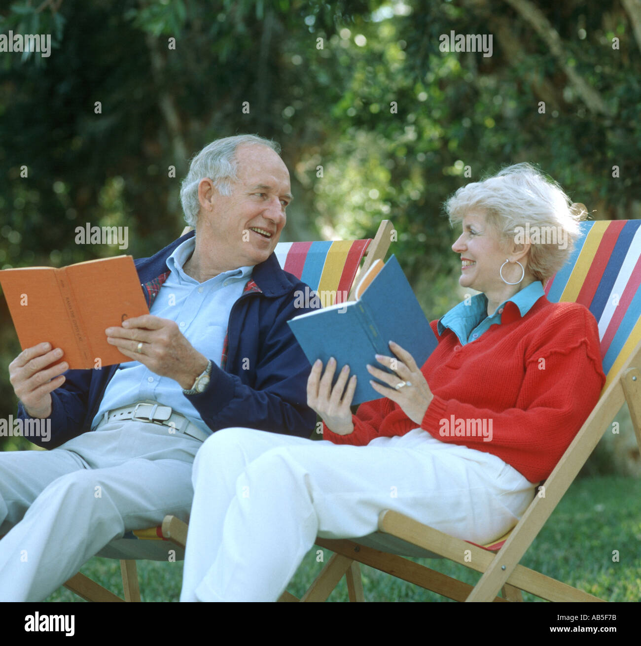 mature couple relaxing in lounges with books - Stock Image